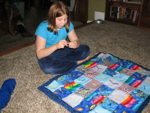 Faith sewing her first quilt.
